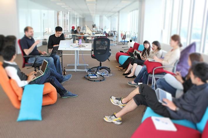 おしゃれなオフィスでミーティング中のHikaruさん(左奥)
